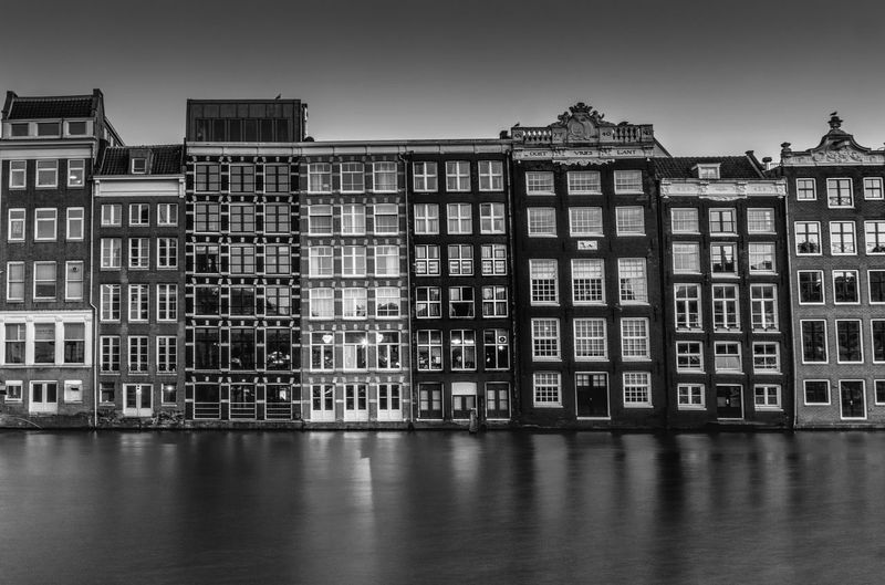 Damrak, Amsterdam B&W Amsterdam Amsterdam Canal Amsterdamcity Architecture Blackandwhite Blackandwhite Photography Building Building Exterior Built Structure Canal City Clear Sky Damrak Day Exterior Façade No People Outdoors Reflection Residential Building Residential Structure Sky Water Waterfront Your Amsterdam