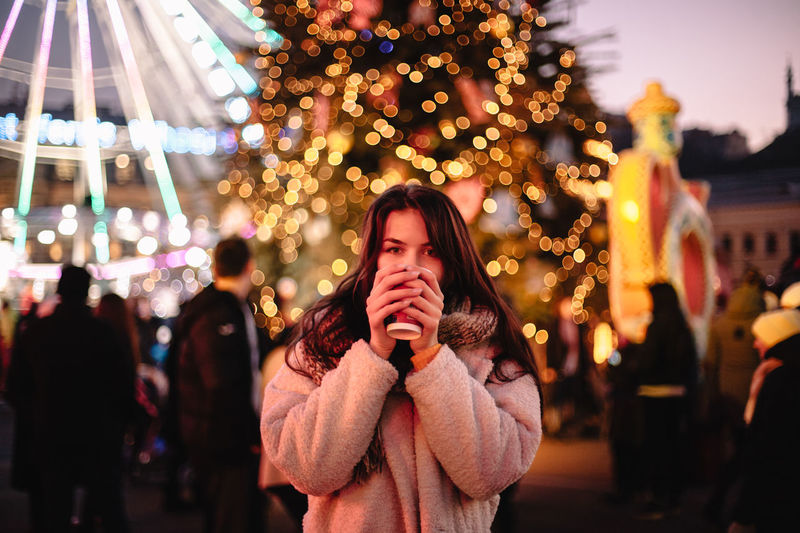 Portrait of young woman standing by illuminated christmas lights at night