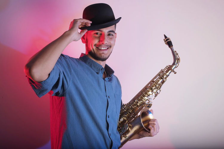 Portrait Of Young Man Wearing Hat Holding Saxophone While Against Wall