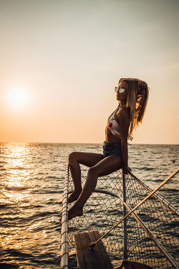 Water Sea Young Adult Sky Leisure Activity Sunset One Person Young Women Lifestyles Real People Beauty In Nature Nature Beauty Scenics - Nature Bikini Women Beautiful Woman Horizon Over Water Sun Hairstyle Outdoors