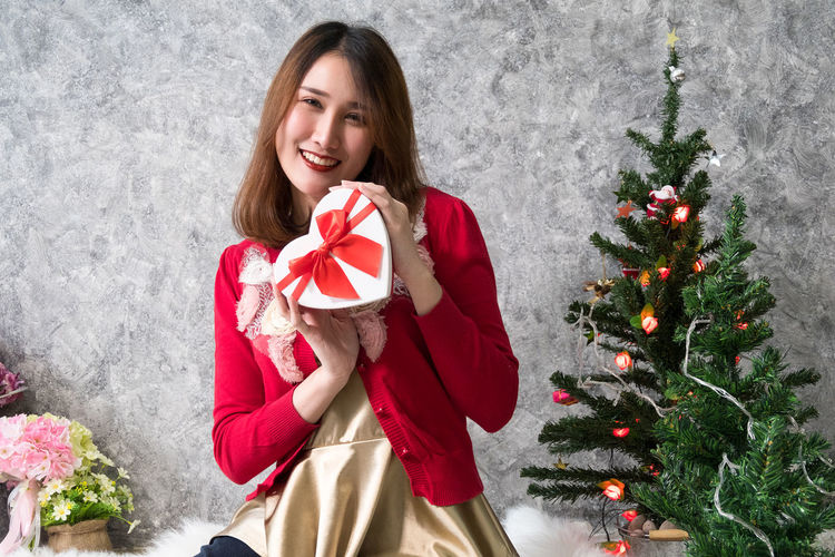 Woman holding gift while sitting at home