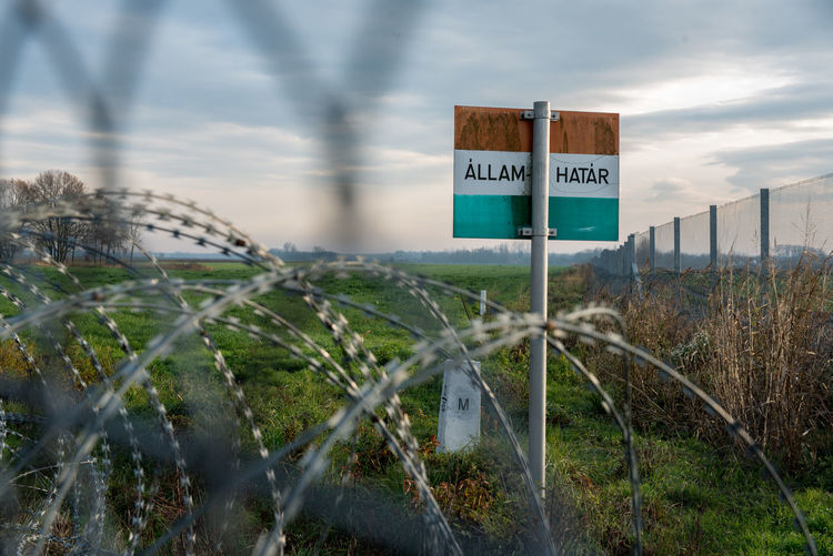 Barbed Wire Hungarian Border Hungary Barrier Border Border Barrier Boundary Cloud - Sky Communication Day Fence Field Guidance Hungarian Border Fence Information Information Sign Land Nature No People Outdoors Plant Road Sign Safety Sign Sky Text Warning Sign Western Script