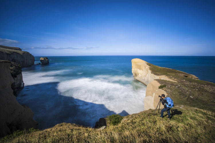 High Angle View Of Man Photographing On Cliff By Sea