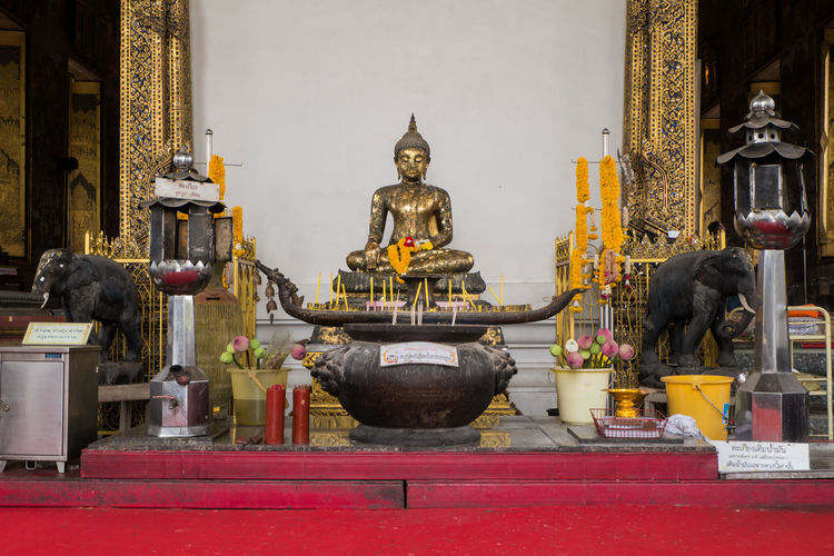 Buddha statue against wall in ancient temple