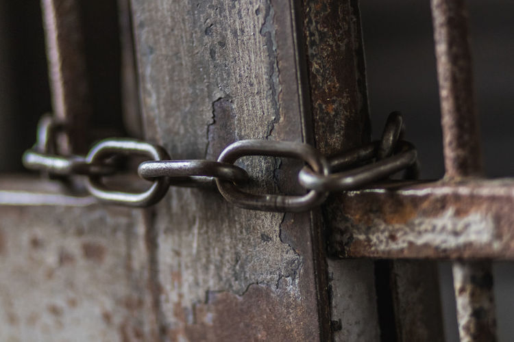Close-up of rusty chain on metal gate