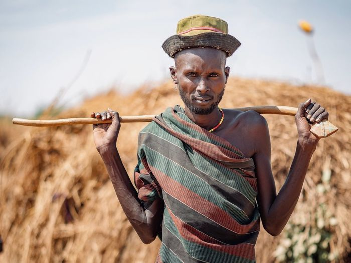 Tribal Ethiopian Photography 🇪🇹 Omo Valley Portraits Dassanech Tribe Ethiopian African Africa Ethiopia Portrait Photography Front View One Person Real People Portrait Clothing Looking At Camera Lifestyles Young Adult Standing Nature Waist Up Day Leisure Activity Sky Smiling Casual Clothing Young Men Land Outdoors Scarf