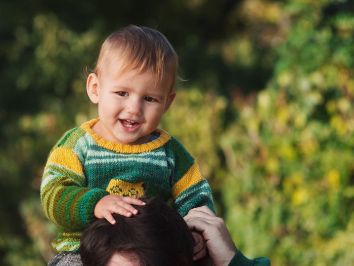 Portrait Of Cute Boy Sitting On Father Neck Against Tree