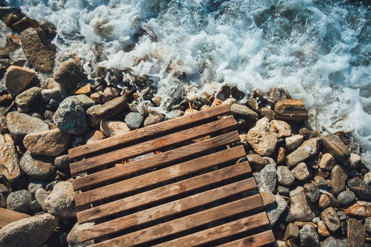 High Angle View Of Water Splashing On Pebbles At Beach