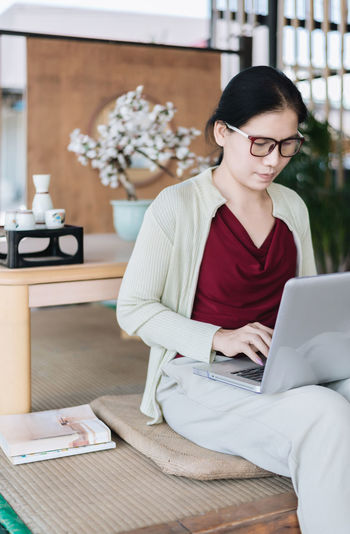 Woman use laptop : Lifestyles Laptop Computer Technology Wireless Technology Woman Eyeglasses  Working Work At Home Domestic Room Domestic Life Sitting Adult One Person Cardigan Trousers