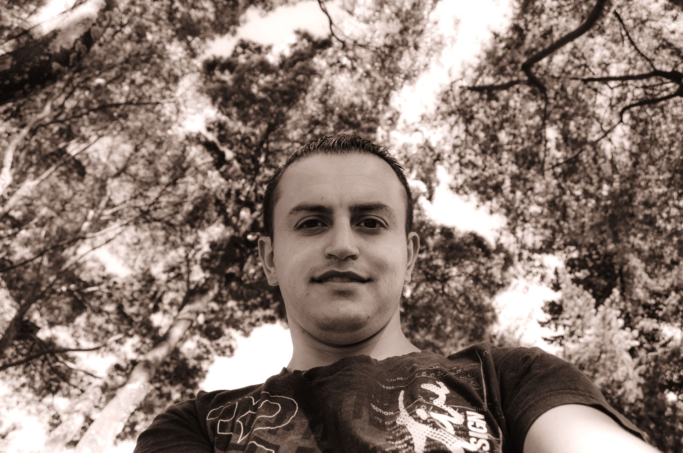 tree, headshot, portrait, looking at camera, lifestyles, young adult, person, leisure activity, front view, forest, young men, head and shoulders, casual clothing, close-up, day, low angle view, outdoors, human face