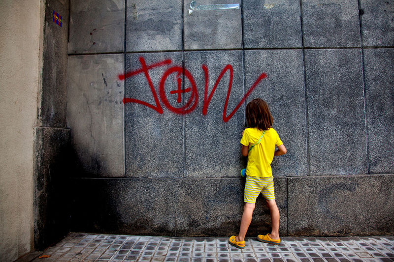 7 year old boy with long hair by wall with graffiti, Barcelona. Barcelona Boredom Building Exterior Built Structure Casual Clothing Childhood City Life Day Full Length Graffiti Horizontal Long Hair One Boy Only One Person Outdoors People Real People Recreational Pursuit Tag Urban