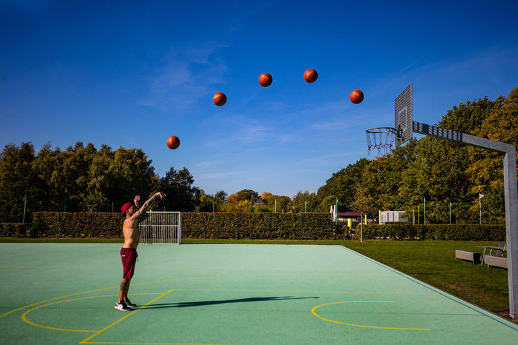Ball Casual Clothing Court Day Full Length Leisure Activity Lifestyles Men Mid-air Motion Nature One Person Outdoors Plant Playing Real People Sky Sport Tree