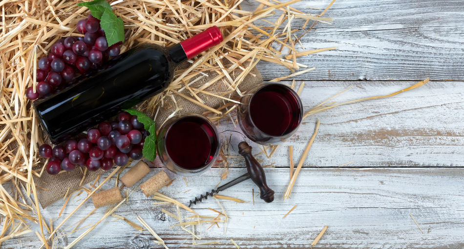 Overhead view of a red wine bottle, drinking glasses, grapes plus corkscrew with straw and burlap on white rustic boards Celebration Merlot Red Wine Alcohol Anniversary Bottle Corkscrew Drink Food And Drink Fruit Grape Overhead View Straw Wine