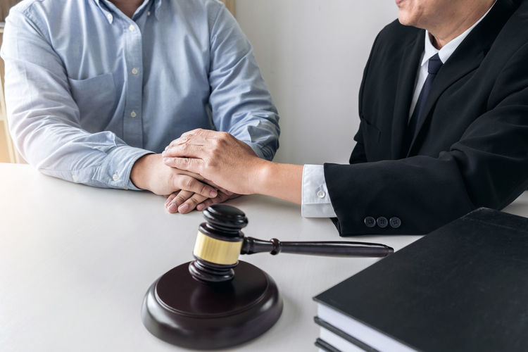 Close-up of lawyer and client with holding hands at desk in courtroom
