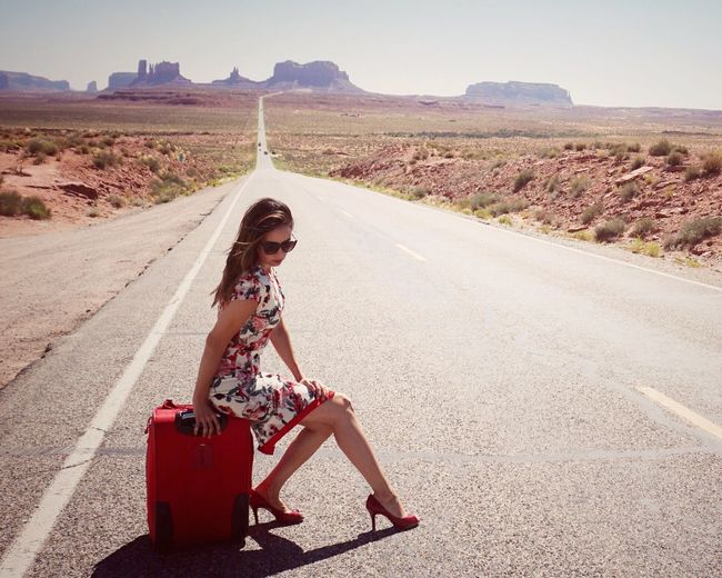 Full length of beautiful woman with luggage on road leading towards monument valley during sunny day