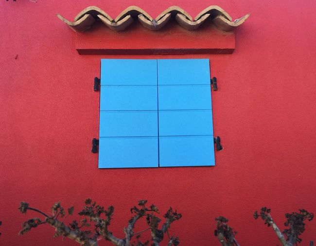 Low angle view of window on red wall