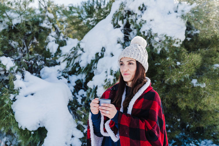 Portrait of man wearing hat standing in snow