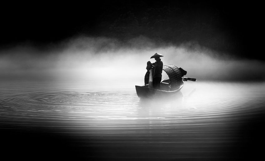 Silhouette people on boat in water
