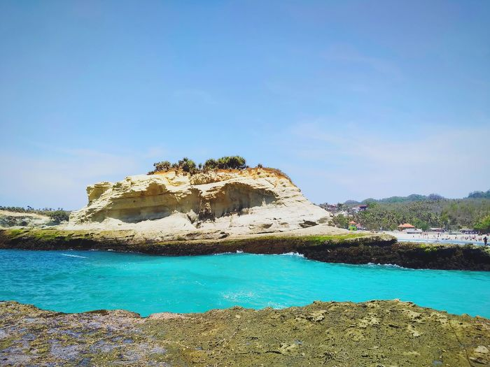 Scenic view of rocks by sea against blue sky