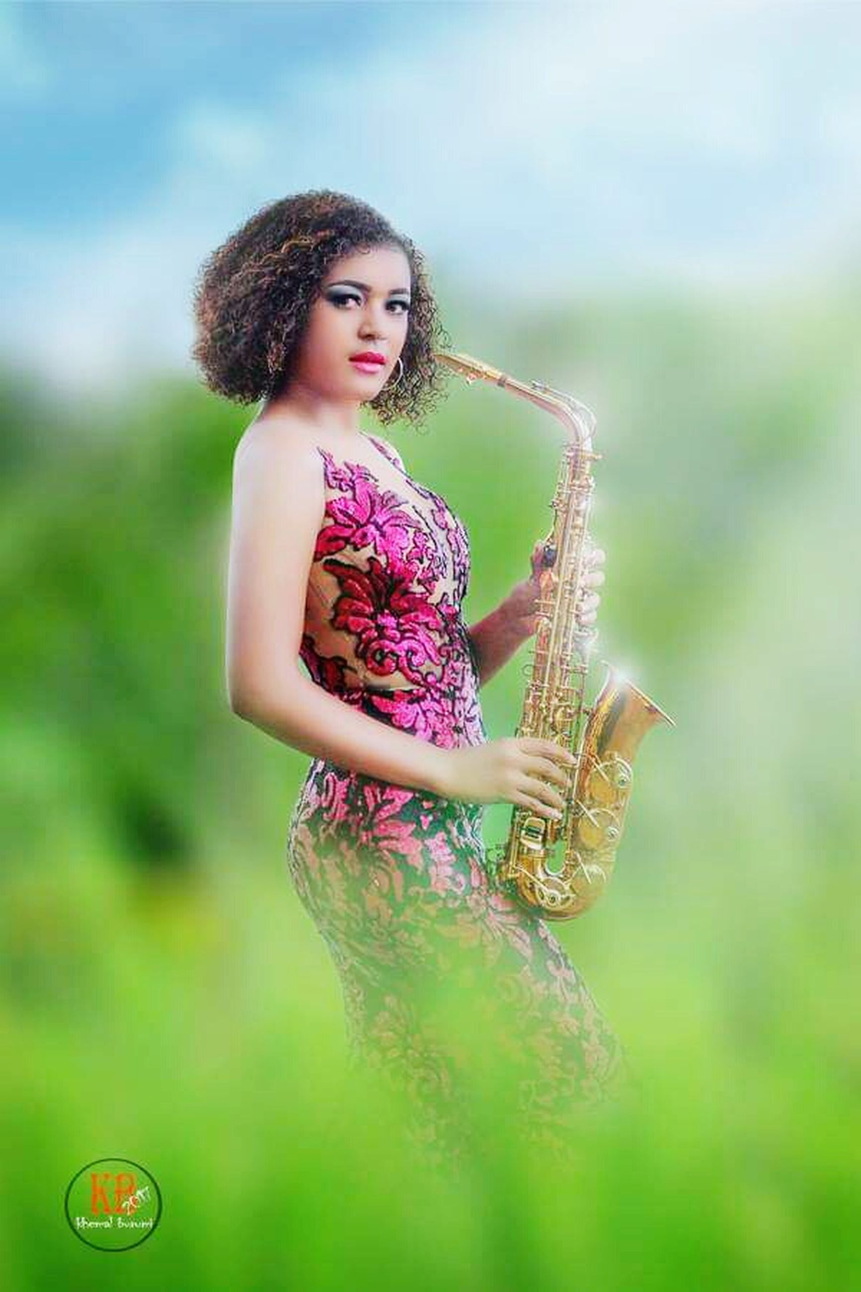 musical instrument, music, one person, beauty, arts culture and entertainment, musician, young adult, adult, clothing, playing, women, beautiful woman, artist, three quarter length, standing, plant, fashion, curly hair, portrait, young women, hair, hairstyle, skill, outdoors