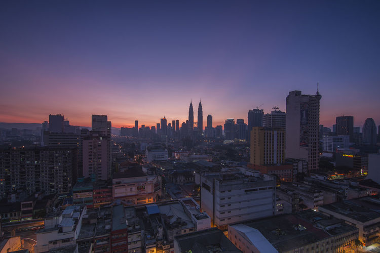 Sunrise skyline of Kuala Lumpur, Malaysia Architecture Blue Building Exterior Built Structure Capital Cities  City City Life Cityscape Development Financial District  Illuminated Modern No People Office Building Orange Color Outdoors Ray Of Light Residential Building Residential District Sky Skyline Skyscraper Tall Tall - High Urban Skyline