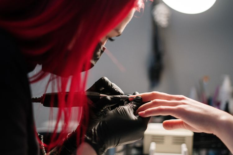 Close-up of woman tattooing customer in studio