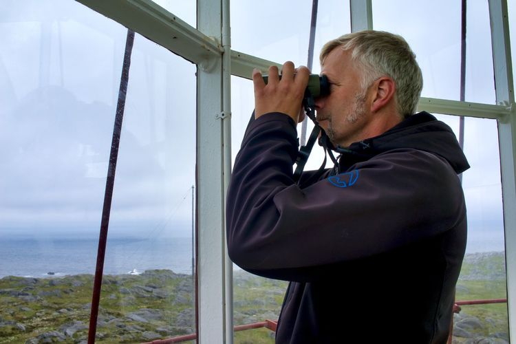Norway, Utsira: man watching through binocular from inside a lighthouse; lighthouse keeper Horizontal Day Adult Binoculars White Hair Grey Hair Gray Hair Looking Watching Profile Portrait Caucasian Hand Hood - Clothing Lighthouse Lighthouse Keeper Real People Men One Person Window Leisure Activity Lifestyles Males  Waist Up Nature Mature Men Glass - Material Sky Mature Adult Standing Holding Casual Clothing Outdoors