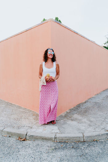 Woman standing by pink umbrella against wall
