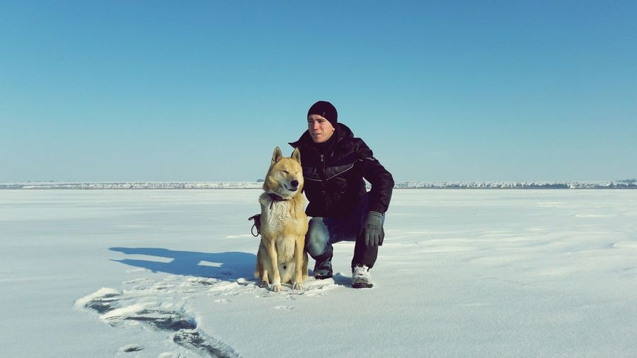 Portrait of man with dog standing on snow