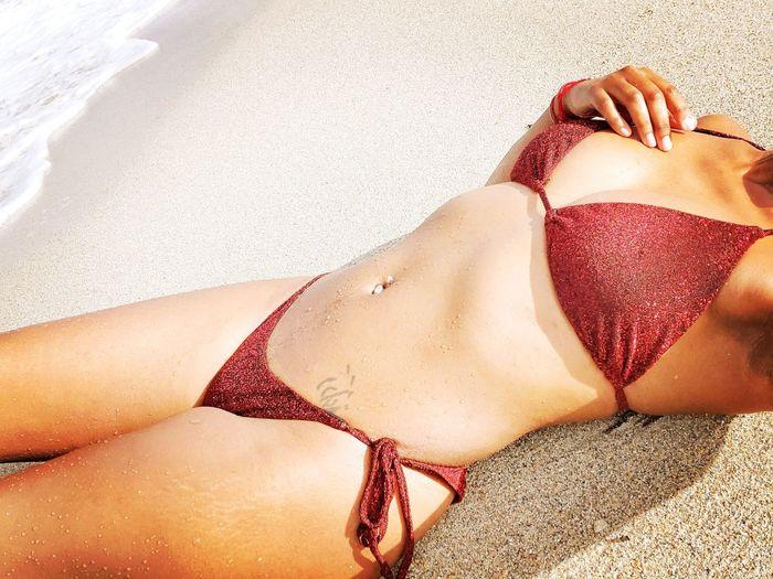 Midsection of sensuous woman wearing bikini lying down at beach