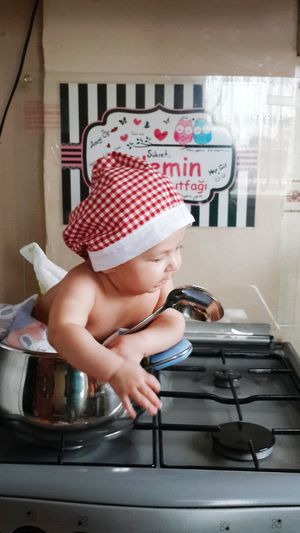 Cute Baby Boy Sitting In Container On Gas Stove Burner At Home
