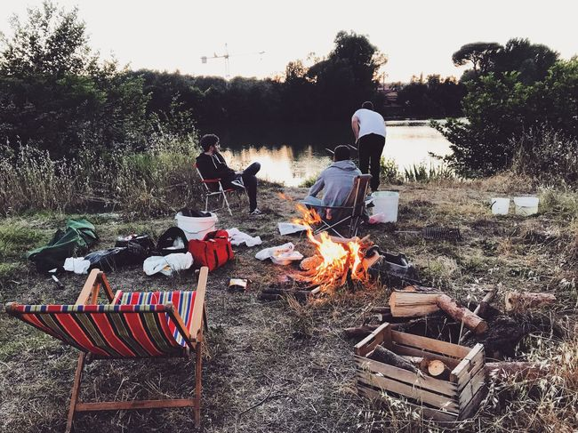 Burning Flame Camping Campfire Bonfire Barbecue Togetherness Heat - Temperature Outdoors Leisure Activity Men Real People People Day Fire Pit Adult Nature Friendship Adults Only Sky Riverside River