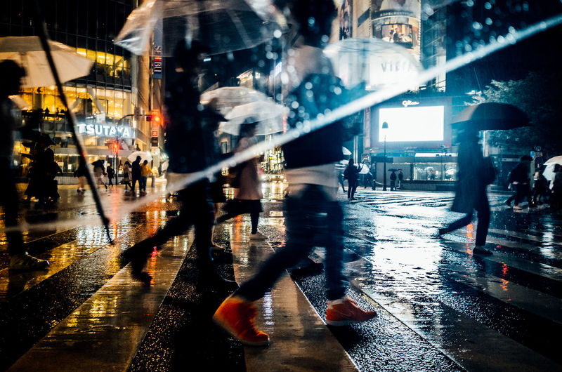 Blurred motion of people walking on wet street at night
