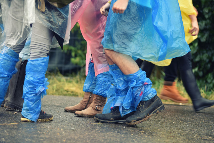 Low section of people tied polythene bag on leg while walking on street