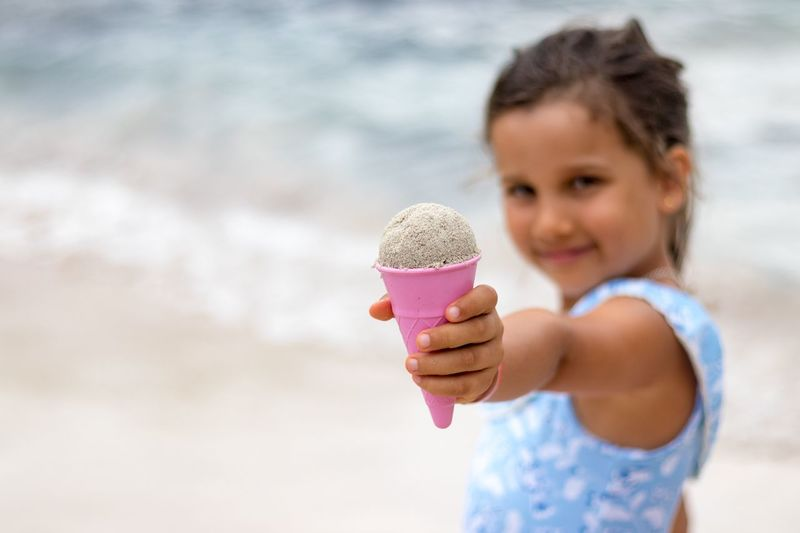 Portrait Of Girl Holding Sand In Cone While Standing At Beach