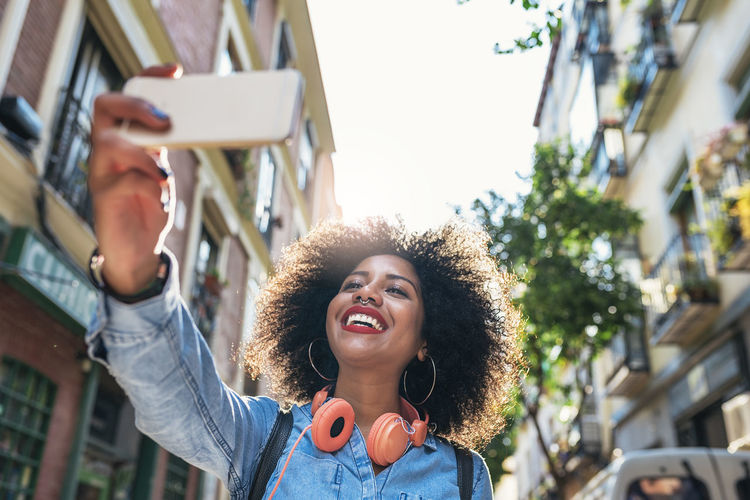 Self portrait of beautiful young afro american Concept. Adult African Afro American Beautiful Casual Copy Space Hair Headphones Woman Adult Attractive Beautiful Black Copy Space. Curly Hair Ethnic Hairstyle Mobile Phone One Person Outdoors Photo Portrait Selfie Urban