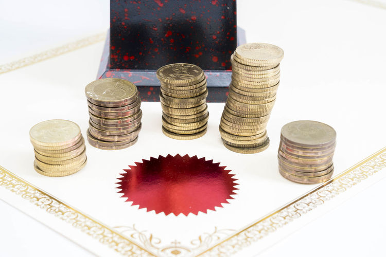 Trophy Cup and coins and blank certificate on white background Finance Still Life Coin Indoors  Business Wealth Large Group Of Objects Studio Shot Stack Currency White Background Close-up High Angle View No People Savings Arrangement Red Strategy Investment Shape Economy