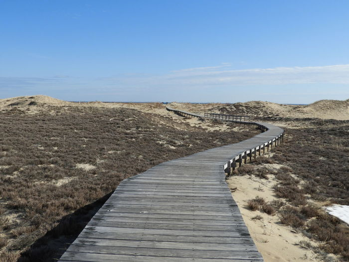 Boardwalk Amidst Land Against Sky