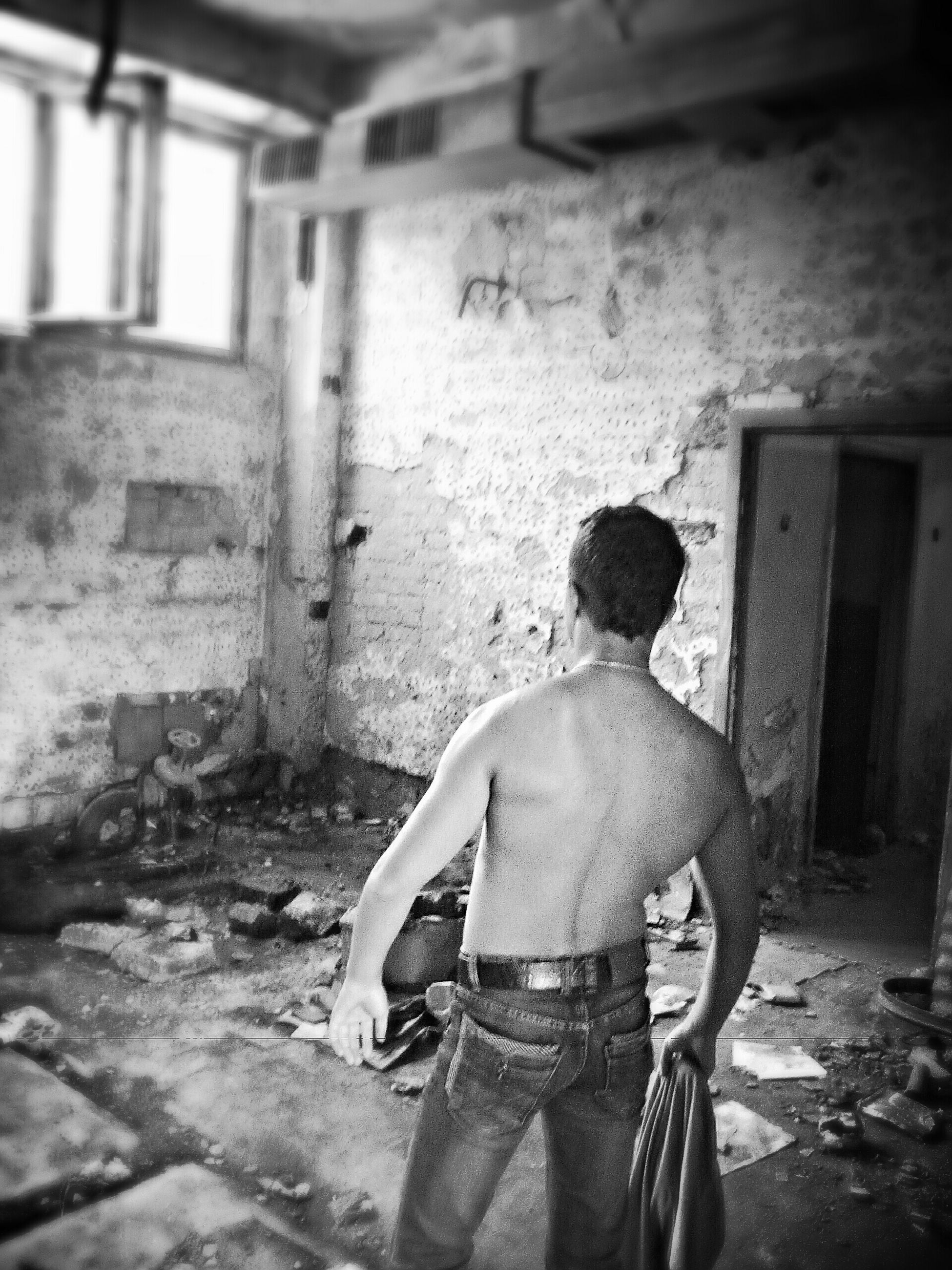 lifestyles, casual clothing, built structure, architecture, leisure activity, standing, rear view, full length, indoors, men, abandoned, three quarter length, building exterior, holding, wall - building feature, side view, day, old