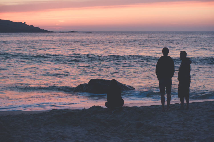 Silhouette People On Seashore During Sunset