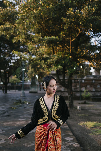 Young woman wearing traditional clothing standing on footpath against trees in park