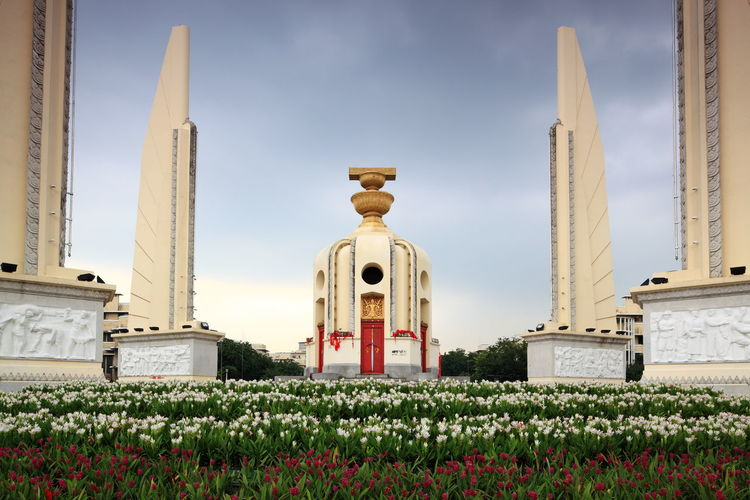 Flowers at democracy monument against sky