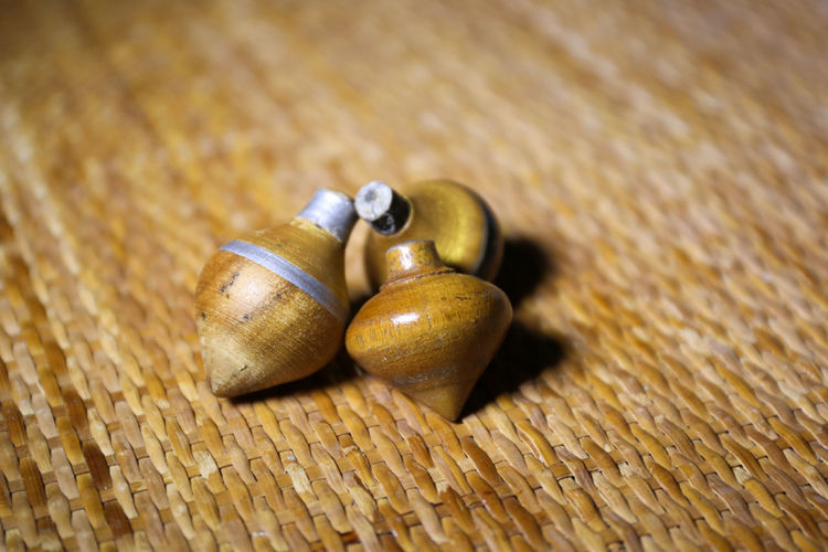 Close-up of wooden spinning tops on mat