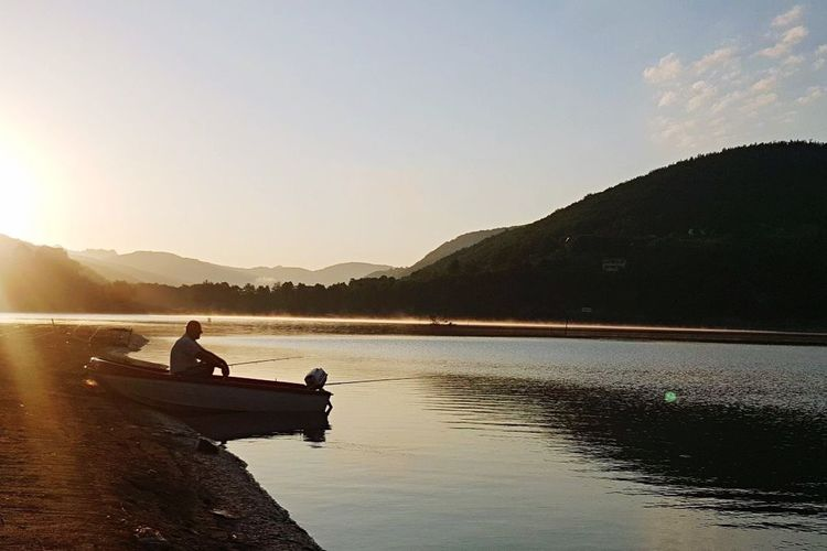 Mountain Lake Sky Water Silhouette Transportation Outdoors Nature Leisure Activity Nautical Vessel Real People Sitting Day Scenics Rowing Beauty In Nature Men Sunset One Person Full Length Fisherman Fishing Fishing Boat Fishing Time Ribariće