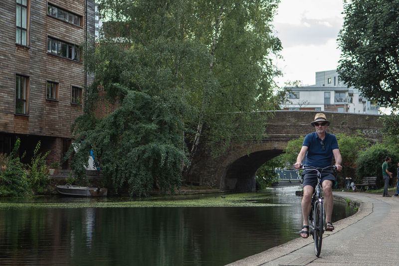 Man riding bicycle by canal