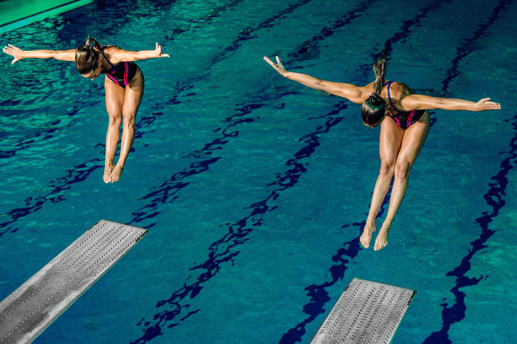 Two Female Divers On Training Or Competition. Diving Diver Swimming Pool Sport Team Double Water Women Jumping Females Jump Diving Board Board Above Action Extreme Sports Swimwear Water Sport Activity Swim Active Blue Training Exercising Two People