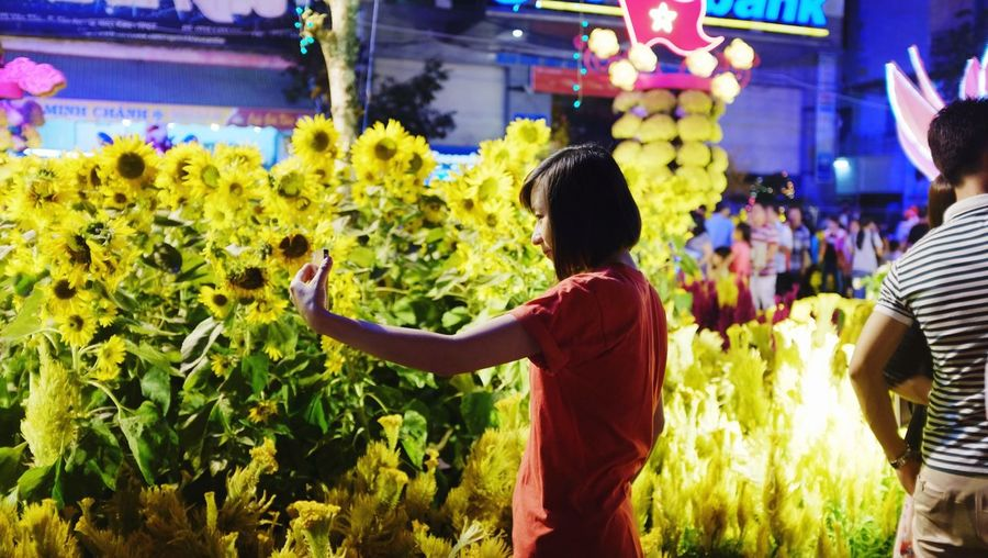 Teenage girl taking selfie by sunflower plants in city