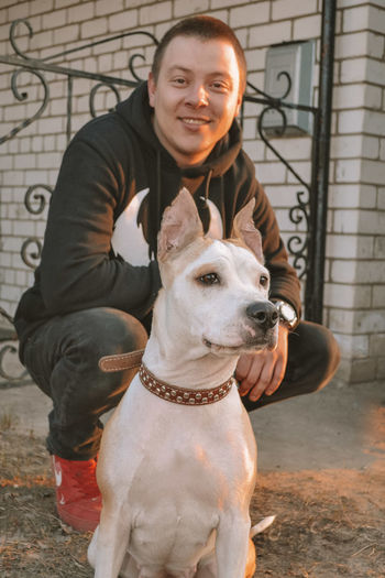 Portrait of man with dog sitting outdoors