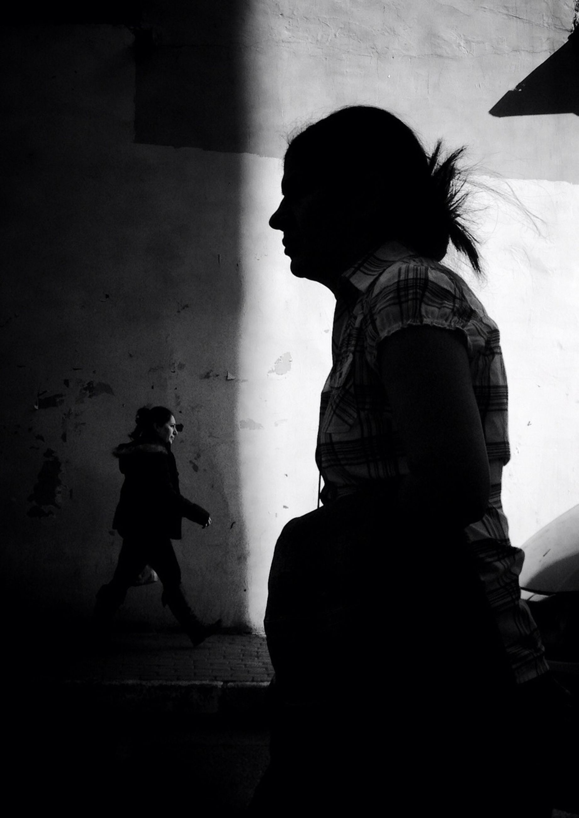full length, lifestyles, leisure activity, casual clothing, rear view, indoors, built structure, architecture, childhood, wall - building feature, standing, shadow, side view, walking, silhouette, boys, men, sunlight