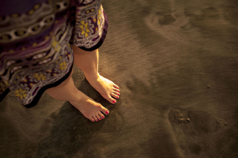 Low Section Of Woman Standing On Sandy Beach